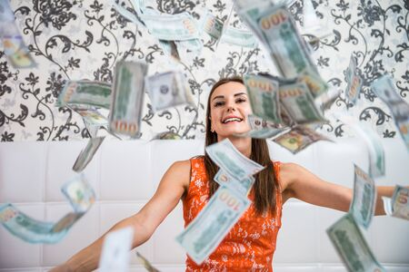 Photo pour lot of banknotes fly in the air on a girl lying on a white bed in slow motion. Huge wealth of money. - image libre de droit