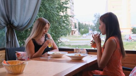 Foto de Two long-haired girls are resting in a cafe with a modern interior and laughing. Indoor portrait of funny smiling ladies in fashionable clothes drinking fruit smoothies - Imagen libre de derechos
