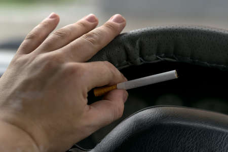 close-up, the hand of the driver of the car with skin disease vitiligo holds a cigarette