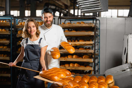 Foto für Young bakers with a wooden shovel with bread in their hands against the background of shelving with bread in a bakery. Industrial bread production - Lizenzfreies Bild