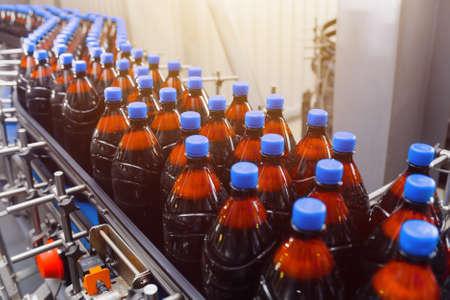 Plastic bottles with beer on a conveyor belt. Industrial beer production