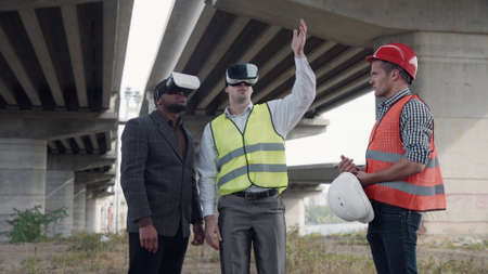 Photo pour 4K shot of business team of two architects and afro american foreman in suit uses virtual reality glasses to discuss a project of development while standing under overpass construction. - image libre de droit