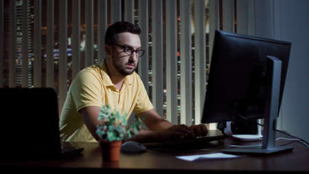 Man in glasses sitting at computer in office and working at night.
