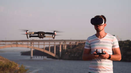 Young man wearing VR headset and controlling flying drone on background of river.