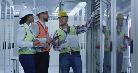 Photo for Group of multiethnic men and woman in hardhats working in hall of solar plant control center having discussion between racks - Royalty Free Image