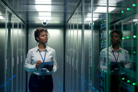 Foto de African American woman using tablet while walking in corridor of data center and checking hardware on server racks - Imagen libre de derechos