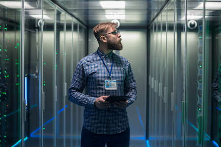 Photo pour Portrait of adult bearded man glasses standing in corridor of server room in data center smiling at camera - image libre de droit