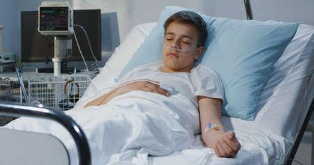 Medium shot of teenager boy lying in hospital bed