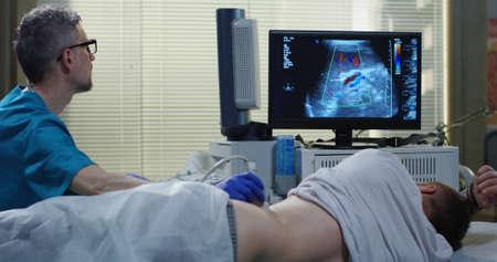 Foto de Medium shot of a doctor performing an ultrasound examination on a man - Imagen libre de derechos