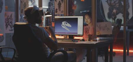 Foto de Medium shot of a VR headset wearing young man modeling dinosaur skull on computer - Imagen libre de derechos