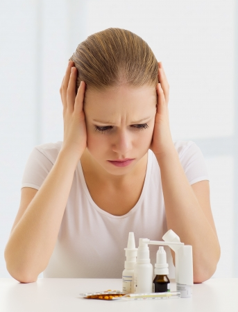 woman with a headache and with medicines