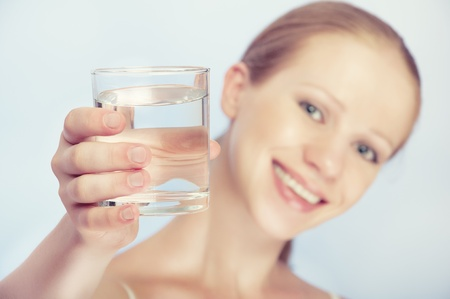 face of a young healthy woman and a glass of clean water