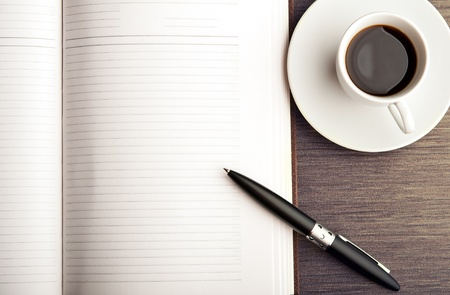 Photo pour Open a blank white notebook, pen and cup of coffee on the desk - image libre de droit