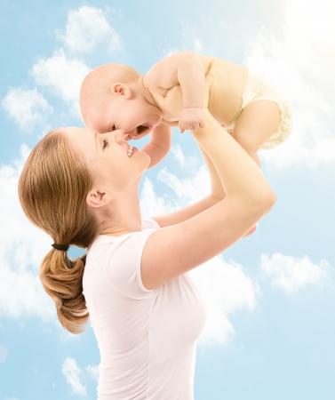 Foto de happy family. Mother throws up and kissing baby in the sky in nature - Imagen libre de derechos