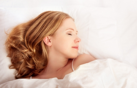young beautiful woman sleeping in white bed netの写真素材