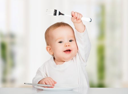 Funny happy baby with a knife and fork eating food