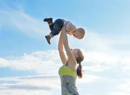 Mother throws up  baby in the sky in nature