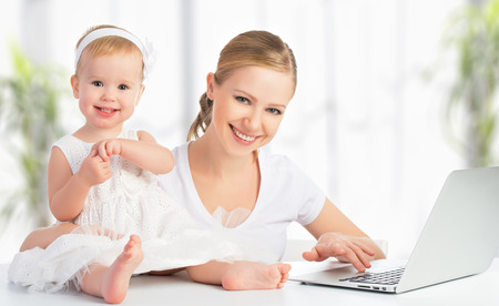 happy family mother and baby at home using laptop computer