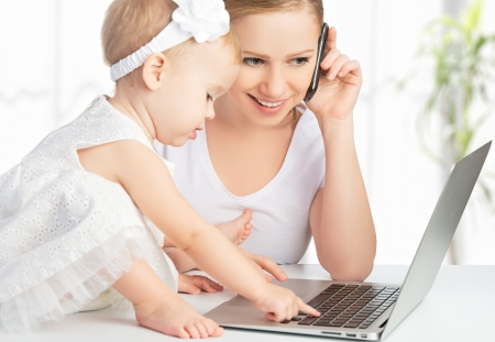 Photo pour young mother with baby daughter works on the Internet with a computer and phone - image libre de droit