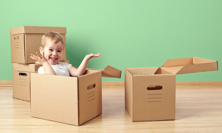 happy baby toddler sitting in a cardboard box empty room
