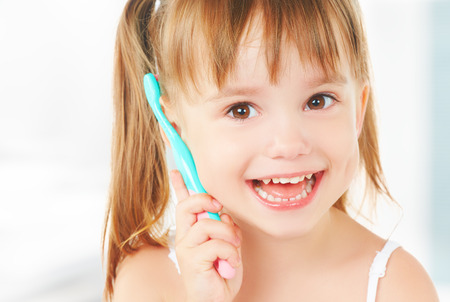Photo pour dental hygiene. happy little girl brushing her teeth - image libre de droit