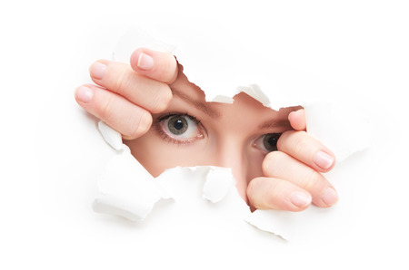 eyes of a young curious woman peeking through a  hole torn in white paper poster