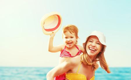 Foto de happy family on the beach. mother and baby daughter  at sea - Imagen libre de derechos