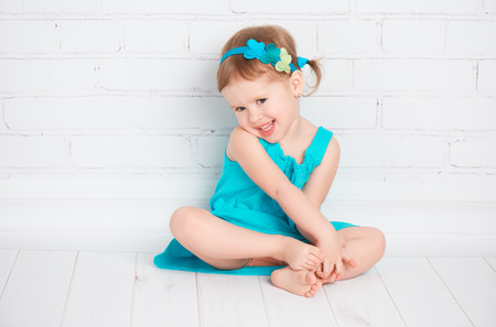 beautiful little baby girl in a turquoise dress on the floor near a white brick wall