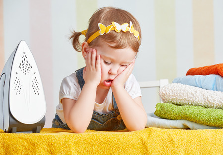 tired   cute little baby girl housewife iron clothes iron, is engaged in domestic work
