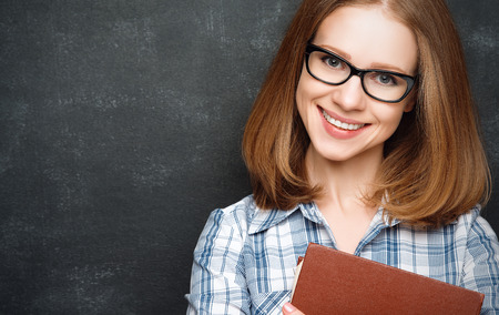 Photo pour happy girl student with glasses and a book from the  blackboard - image libre de droit