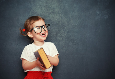 Photo for happy little girl schoolgirl with a book from the blackboard - Royalty Free Image