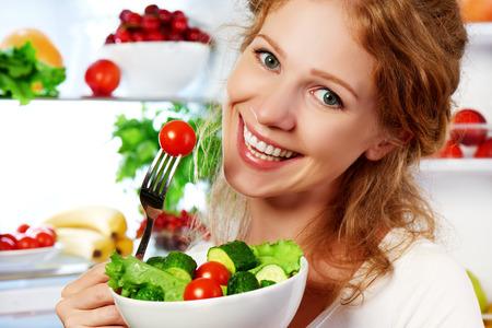 Foto de happy woman eats healthy food vegetable vegetarian salad about refrigerator - Imagen libre de derechos