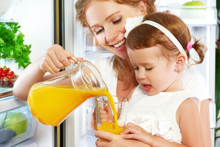 Photo pour happy family mother and baby daughter drinking orange juice in the kitchen near the refrigerator - image libre de droit