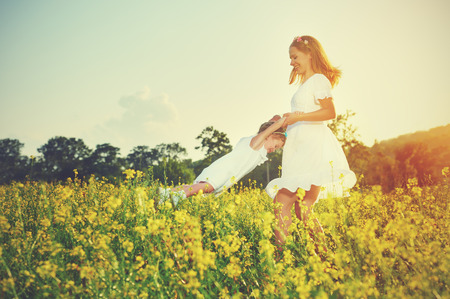 happy family plays in summer meadow, mother and little daughter girl child  with yellow flowers