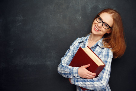 happy girl student with glasses and a book from the  blackboard