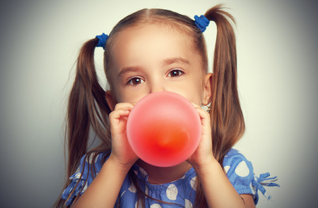 child little girl in a blue dress inflates a red balloon