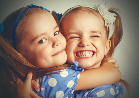 Foto de Happy funny girl twins sisters hugging and laughing - Imagen libre de derechos