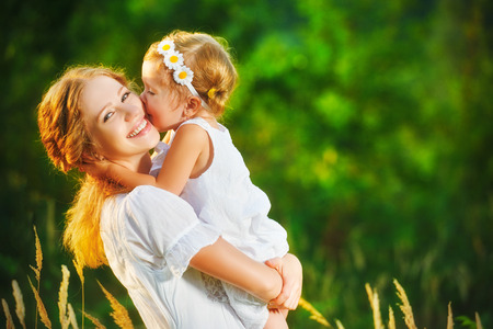 Happy family on a summer meadow. little girl child baby daughter hugging and kissing mother