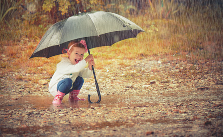 happy baby girl with an umbrella in the rain runs through the puddles playing on natureの写真素材