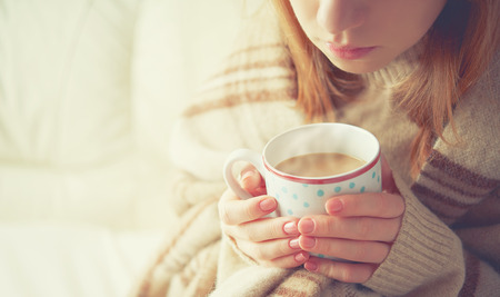 Photo pour warm cup of hot coffee warming in the hands of a girl - image libre de droit