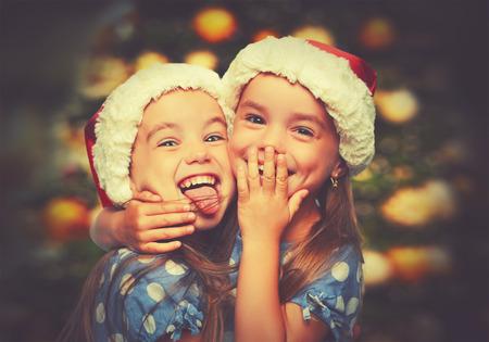 Foto de Christmas Happy funny children twins sisters hugging - Imagen libre de derechos