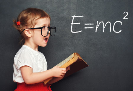Photo pour wunderkind little girl schoolgirl with a book from the blackboard with physical formulas - image libre de droit
