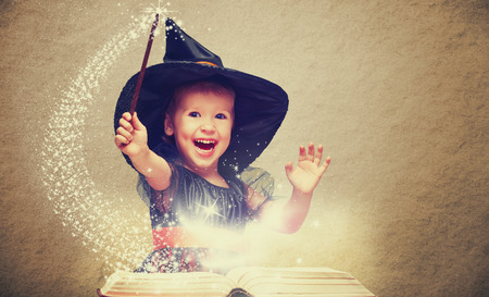 Photo pour Halloween. cheerful little witch with a magic wand and glowing book conjure and laughs. - image libre de droit