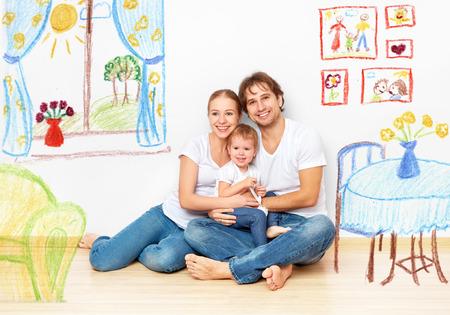 Foto de Concept family: Happy young family in the new apartment dream and plan interior - Imagen libre de derechos