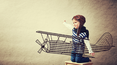 Photo pour Happy baby dreams of becoming a pilot aviator and plays with planes on background wall of house - image libre de droit