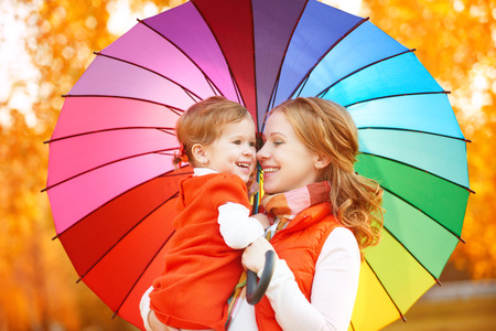 Happy family mum and child daughter with rainbow colored umbrella under rain on nature