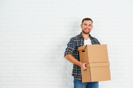 Foto de moving to a new apartment. Young happy man with cardboard boxes around the white brick wall - Imagen libre de derechos