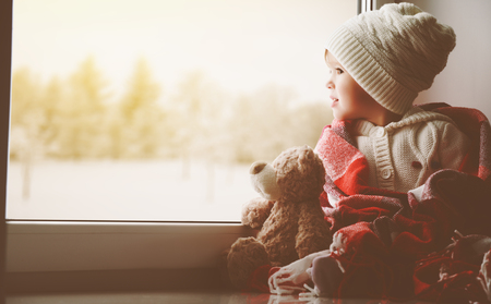 child little girl sitting by the window with a teddy bear and looking at the winter forest