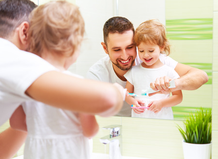 Photo pour Happy family father and daughter child girl brushing her teeth in the bathroom toothbrushes - image libre de droit