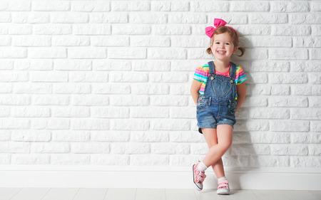 Foto de Happy child little girl laughing at a blank empty brick wall - Imagen libre de derechos